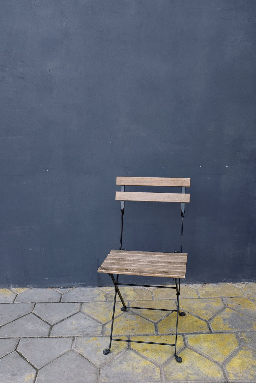 gray wall and brown wooden chair